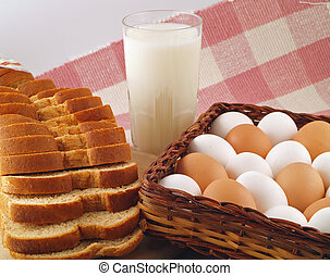 A glass of milk, a loaf of sliced wheat bread and a bunch of brown and white eggs - the grocery list staples.