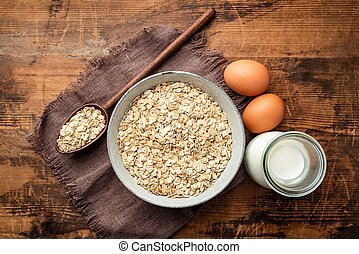 Milk, eggs and oat flakes on old wooden table background