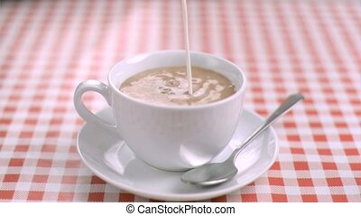 Milk flowing in super slow motion in a cup of tea in a...