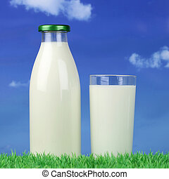 Milk in a bottle and glass on green meadow