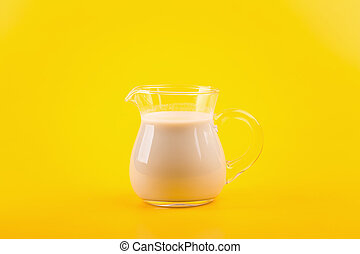 milk in glass on yellow background