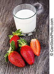 Milk in glass with strawberries on wooden table