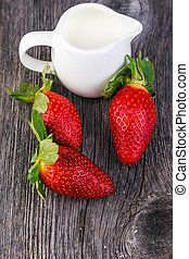 Milk in jug with strawberries on wooden table