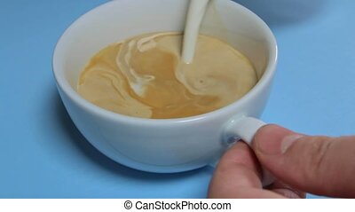 milk is poured into a coffee mug to make a cappuccino.