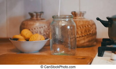 Milk is Poured into a Transparent Jar on a Background of Home Kitchen. Slow Motion in 96 fps. The cook pours milk in a transparent bowl for cooking. Healthy foods. Healthy eating, diet and drinks concept.