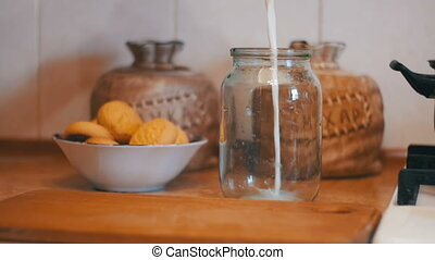 Milk is Poured into a Transparent Bank on a Background of Home Kitchen. Slow Motion