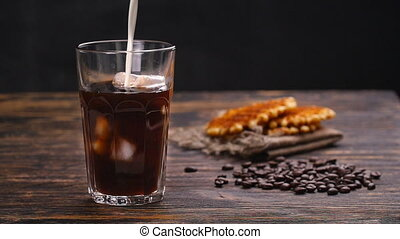 Milk is poured into coffee - Milk or cream is poured into...