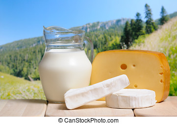 Milk jug and cheese against mountains in background