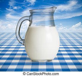 Milk jug on blue tablecloth