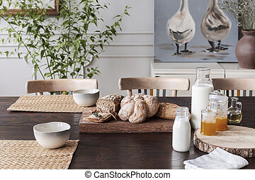 Milk, natural honey and bread on cottage wooden table in dining room interior with poster. Real photo