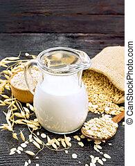 Oat milk in a jug, flour in bowl, oatmeal in a spoon, grain in bag, oaten stalks on a wooden board background