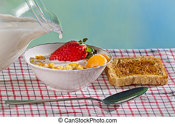 Milk pouring down into fresh fruit and corn flakes