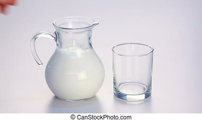 Milk pouring from jug - Hand taking jug of milk and pouring...