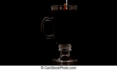 Milk pouring into coffee in a glass