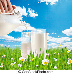 Milk pouring into glass in grass