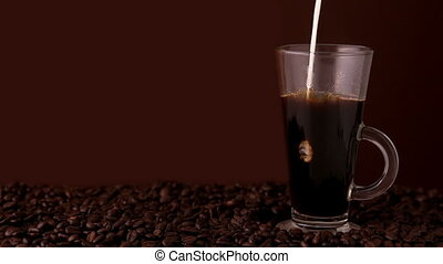 Milk pouring into glass of coffee