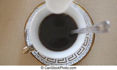 Milk pouring into tea. Close up Slow motion