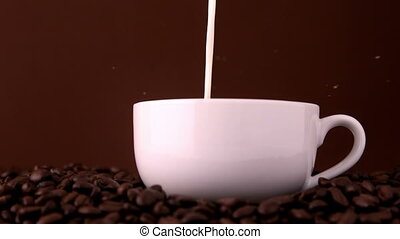 Milk pouring into white coffee cup in slow motion