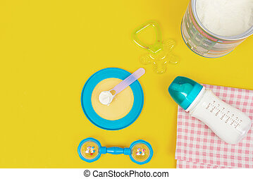 Milk powder for baby in measuring spoon in can and milk bottle on fabric on yellow background