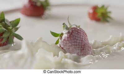 Milk splash on a ripe red strawberry fruit, which lies on a ...