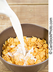 Milk with cereals - Delicious corn flakes with milk on white...