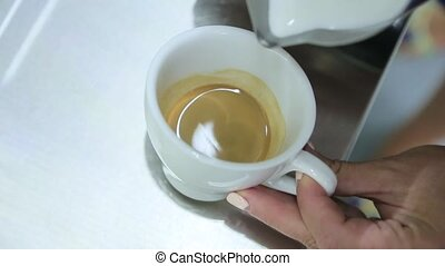 Milk with foam is poured into the cup of coffee