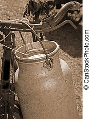 milkman old bicycle with can of milk and ancient sepia toned