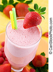 Milkshake in a glass with straws and fresh strawberry.
