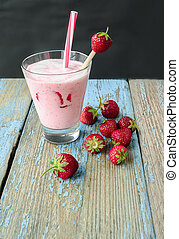 Milkshake with fresh strawberries on an old wooden surface