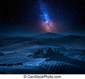Milky way over farm of olive groves and vineyards, Tuscany
