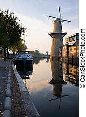 Mill and ship with reflection at sunrise