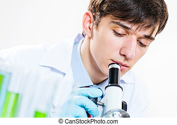 milled scientist looking into a microscope