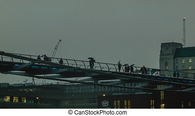 Millenium Bridge in cloudy weather after sunset. People are...