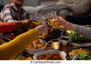 Side view of the hands of a group of young adult multi-ethnic male and female friends sitting at a table at home set for Thanksgiving dinner making a toast with glasses of orange juice