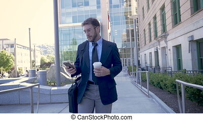 Millennial businessman walking with smartphone turns it...