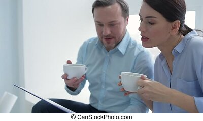 Millennial colleagues drinking tea and discussing project together