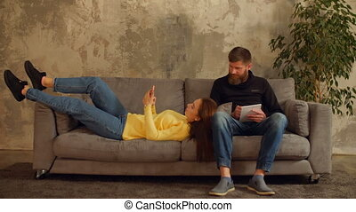 Millennial couple relaxing on sofa in loft apartment -...