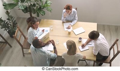 Millennial employees and coach sitting in boardroom view...