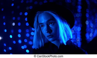 Millennial enigmatic pretty girl blond hairstyle near glowing neon wall at night. Blue hair, hipster hat, nose piercing. Mysterious woman. Slow motion