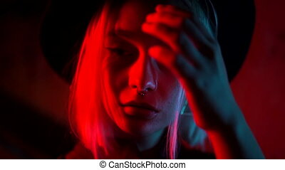 Millennial enigmatic pretty woman with blond dyed hairstyle near glowing neon wall at night. Nose piercing, hipster hat. Mysterious teenager