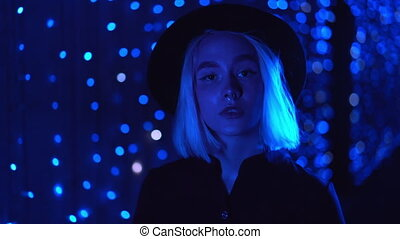 Millennial enigmatic pretty woman with blond hairstyle walking near glowing neon wall at night. Blue hair, hipster hat, nose piercing. Mysterious girl. Slow motion