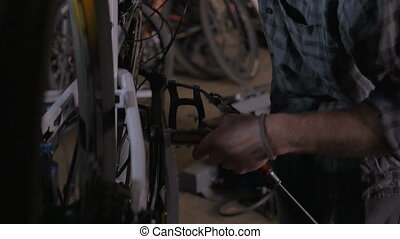 Millennial handsome man working on a mountain bike in repair...