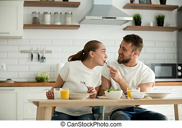 Millennial husband feeding wife with delicious breakfast