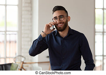 Millennial middle eastern ethnicity businessman talking on phone in office