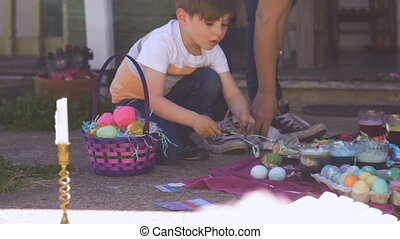 Millennial mother and young son coloring easter eggs...