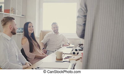 Millennial office workers sit by the table and smile,...