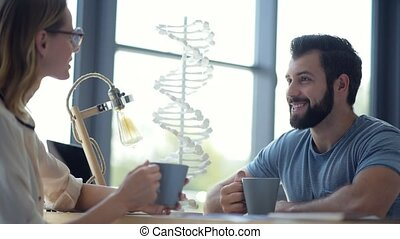 Millennial scientists drinking coffee during lunch break -...