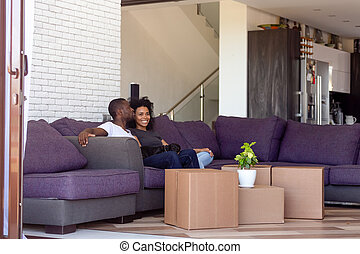 Millennial spouses resting in spacious living room on relocation day