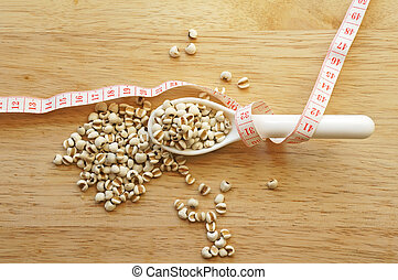 millet in spoon wrapping with measuring tape on wooden table