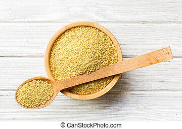 millet in wooden spoon - the millet in a wooden spoon